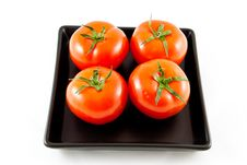 Four Tomatoes On A Black Plate