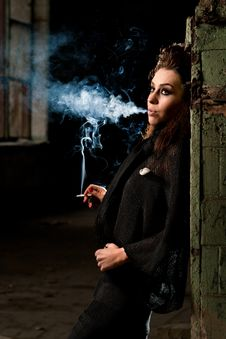 Woman Smokes In The Dark Room Stock Photo