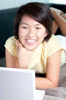Free Young Asian Girl Browsing The Net On Couch Stock Image - 18987281