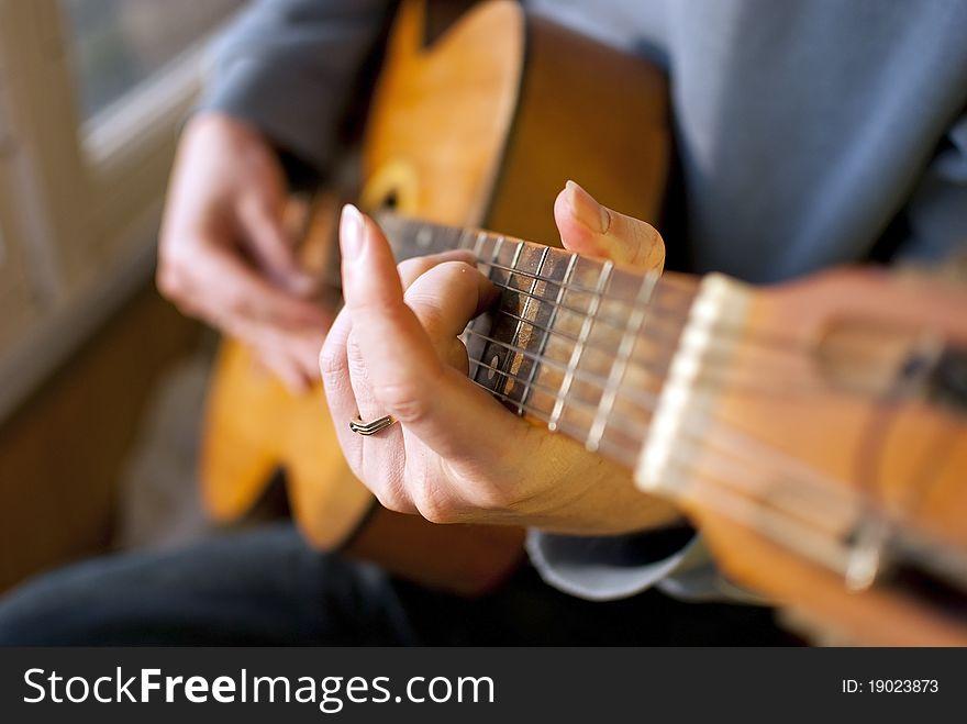 Brown guitar in hands of the guy