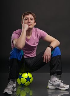Free Man Sits On A Colorful Soccer Ball Royalty Free Stock Photography - 19036217