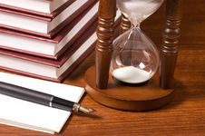 Hourglasses And Book On A Wooden Table Royalty Free Stock Photography