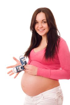 A Pregnant Woman Holding Baby Shoes Stock Image