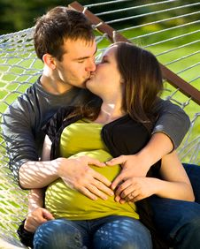 Young Expectant Couple Kissing Stock Photos