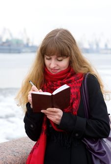 Free Beautiful Girl In The Red Scarf Writing In Notepad Stock Photo - 19077970