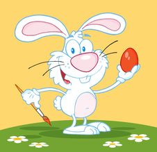 Free White Easter Bunny Painting An Egg Outdoors Stock Image - 19091511