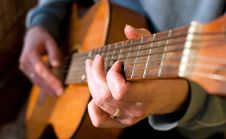 Brown Guitar In Hands Of The Guy Playing It Royalty Free Stock Photo