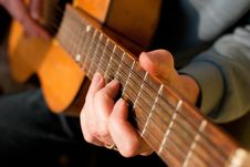 Brown Guitar In Hands Of The Guy Playing It Stock Images