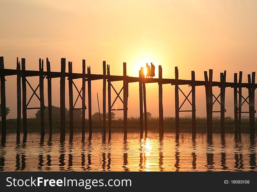 Two monks walk on the wooden bridge