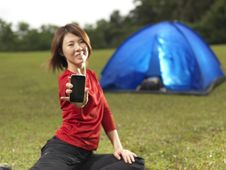 Free Asian Female Camper Showing Her Mobile Phone Royalty Free Stock Images - 19123049