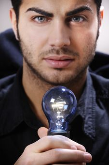 Young Man With Light Bulb In His Hands Royalty Free Stock Photos