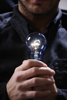 Young Man With Light Bulb In His Hands Royalty Free Stock Images