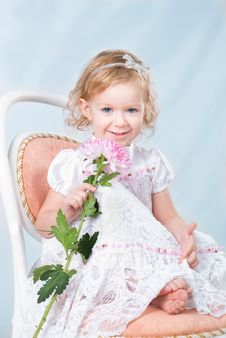 Free Adorable Girl Sitting On The Chair With Flower Royalty Free Stock Image - 19179946
