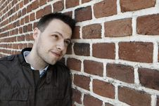 Young Man In Fron Of The Brick Wall Stock Photo