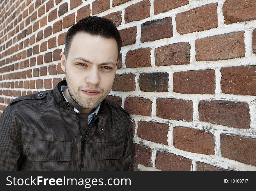 Young man in fron of the brick wall