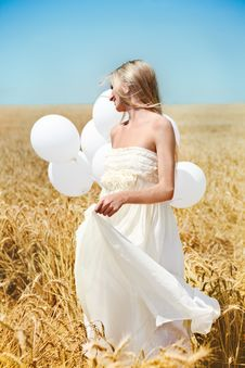 Beautiful Girl With White Balloons In The Field Royalty Free Stock Photography