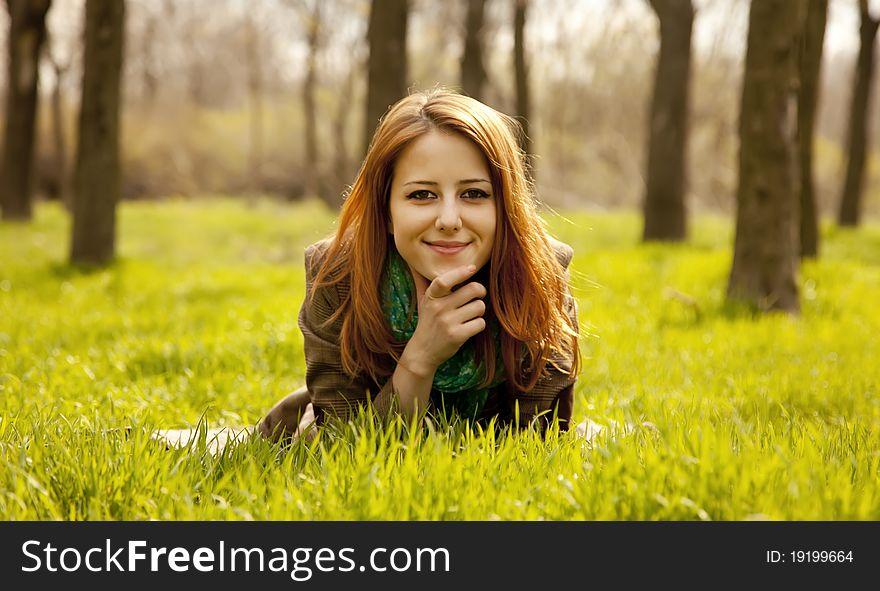 Beautiful girl sitting at green grass at park.