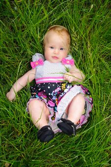 A Beautiful Little Girl Lying In The Grass Stock Photography