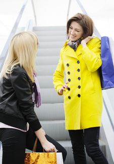 Happy Friends Coming Down A Escalator Holding Shop Stock Photography