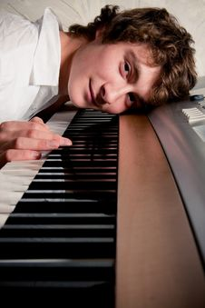 Free Portrait Of A Boy Lying On A Piano Keyboard Royalty Free Stock Photography - 19242907