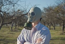 Man In The Gas Mask Surrounded By Leafless Trees. Royalty Free Stock Image