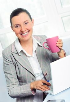 Smiling Young Business Woman With Cup Using Laptop Royalty Free Stock Image