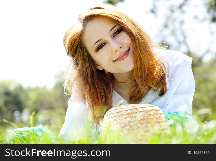 Red-haired girl with hat at the park.