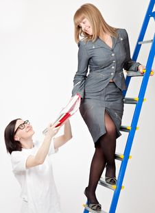 A Woman On A Stepladder With Papers Stock Image