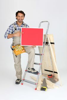 Free Smiling Laborer With Ladder And Red Panel Royalty Free Stock Image - 19322806