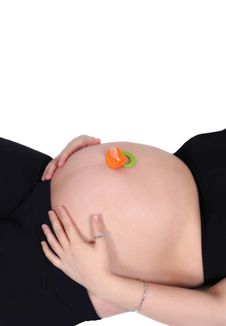 Free Colourful Pacifier Resting On Bare Pregnant Belly Stock Images - 19324934