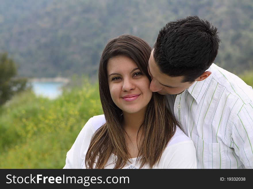 Man Snuggling and Kissing Attractive Woman