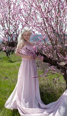Young Pretty Blond Woman In Blooming Garden Stock Image