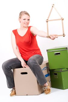 Young Woman With A House Symbol Sits On Moving Box Stock Image