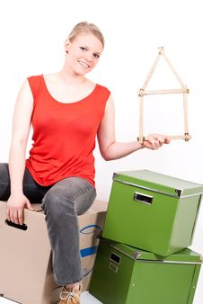 Young Woman With A House Symbol Sits On Moving Box Stock Photos