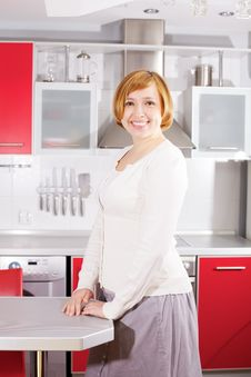 Smiling Beautiful Young Woman Standing At Kitchen Stock Photos