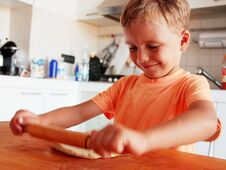 Blond Hair Little Boy Enjoys Making Pizza In The Kitchen Royalty Free Stock Photography