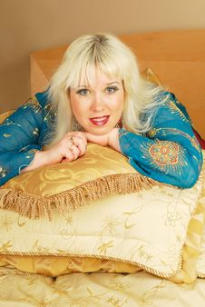 Blond Woman Sitting  With Pillows On A Bed Royalty Free Stock Photo