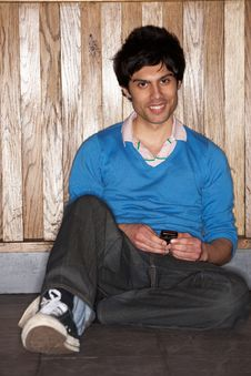 Free Young Man Sitting On Floor With Mobile Phone Royalty Free Stock Photography - 19422887