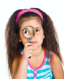 Little Girl Looking Through A Magnifier Stock Image