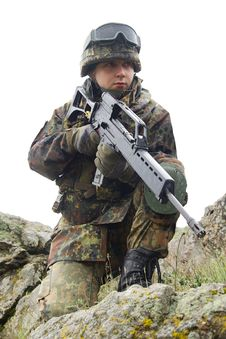 Soldier With Automatic Gun Covering Stock Photography