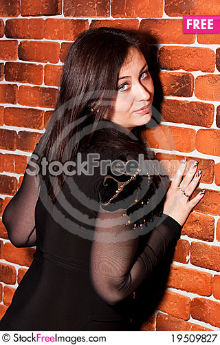 Beautiful woman leaning against brick wall Stock Photo