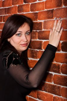 Beautiful Woman Leaning Against Brick Wall Stock Images