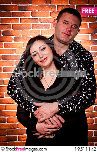 Happy couple standing against brick wall Stock Photo