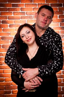 Happy Couple Standing Against Brick Wall Stock Photography