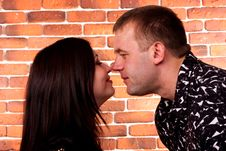 Happy Couple Standing Against Brick Wall Royalty Free Stock Photos
