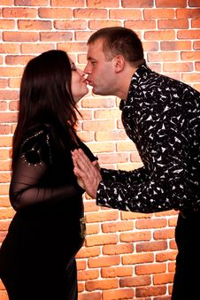 Happy Couple Standing Against Brick Wall Stock Images