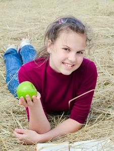Free Girl With An Apple On Dry  Grass Royalty Free Stock Photo - 19527415