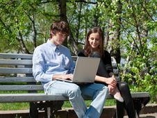 Free Couple Sitting In Park And Using Laptop Royalty Free Stock Photography - 19528747
