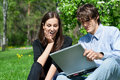 Free Couple Sitting In Park And Using Laptop Royalty Free Stock Photography - 19539787