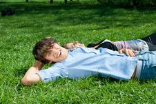 Young Couple Lying On The Grass In Park Royalty Free Stock Photos